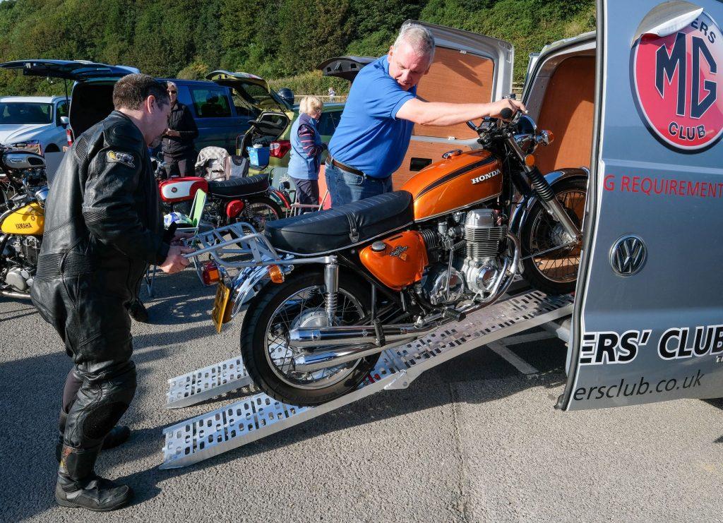 Two men load a classic orange Honda motorcycle into a silver camper van RV