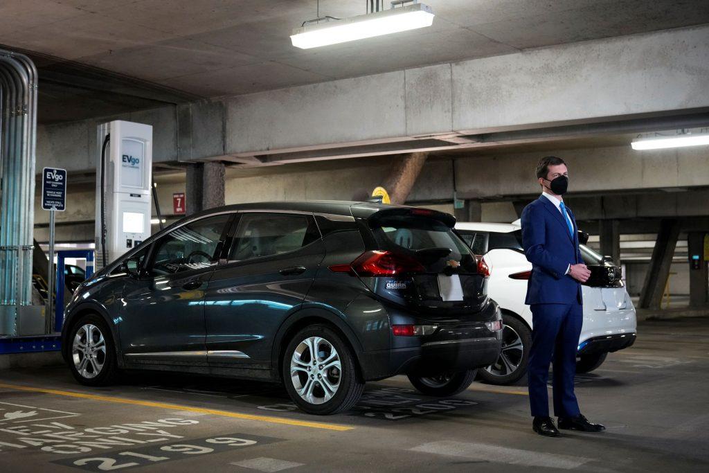 US Secretary of Transportation Pete Buttigieg by an EVgo public EV charging station in a parking garage