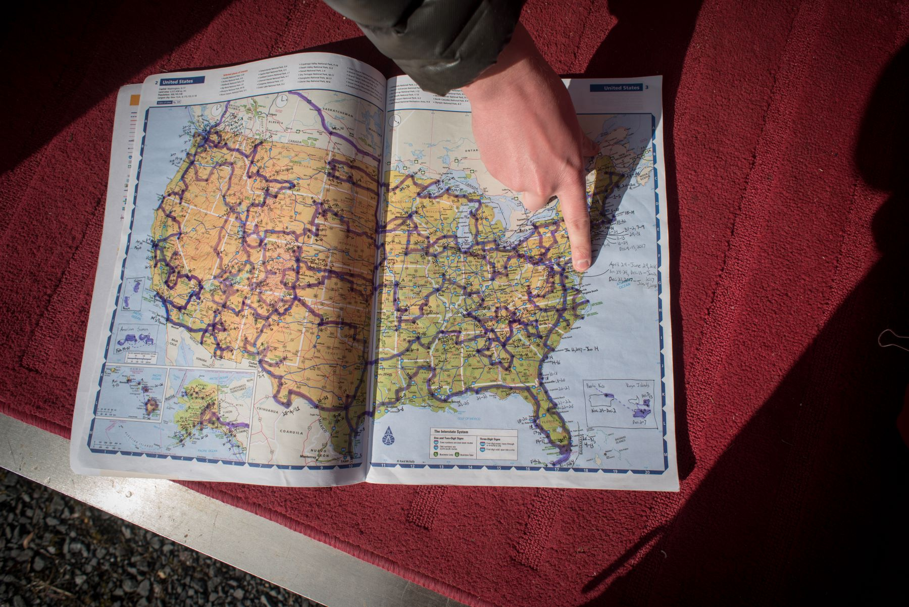 Someone pointing to a location on a map of the United States