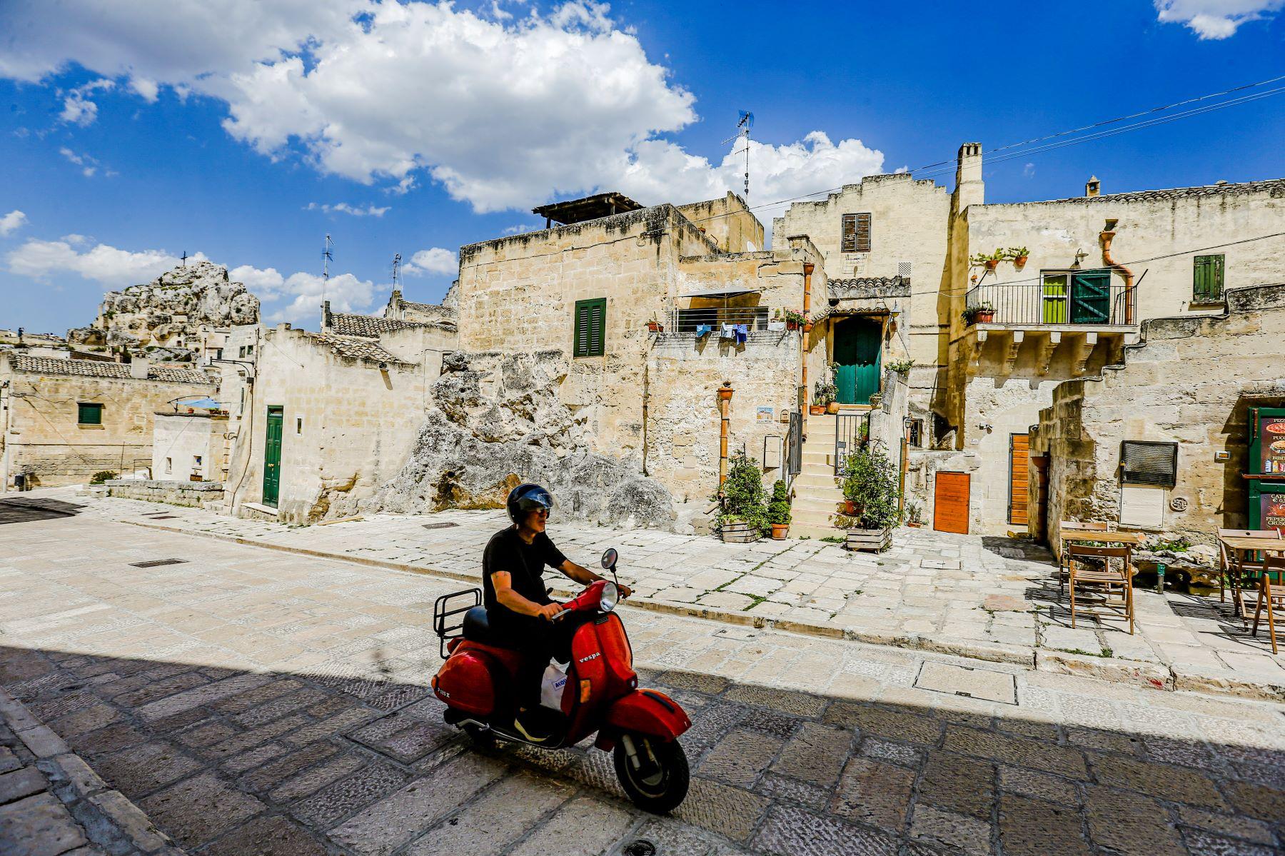 A man driving a Vespa scooter in Basilicata, Italy