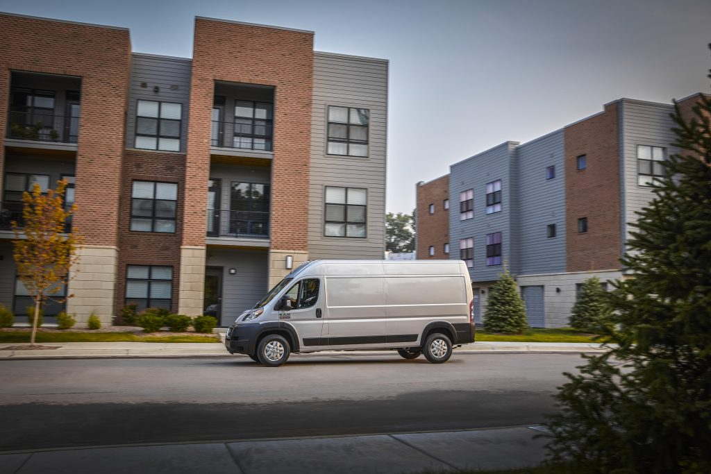 White 2022 Ram ProMaster driving by apartment buildings