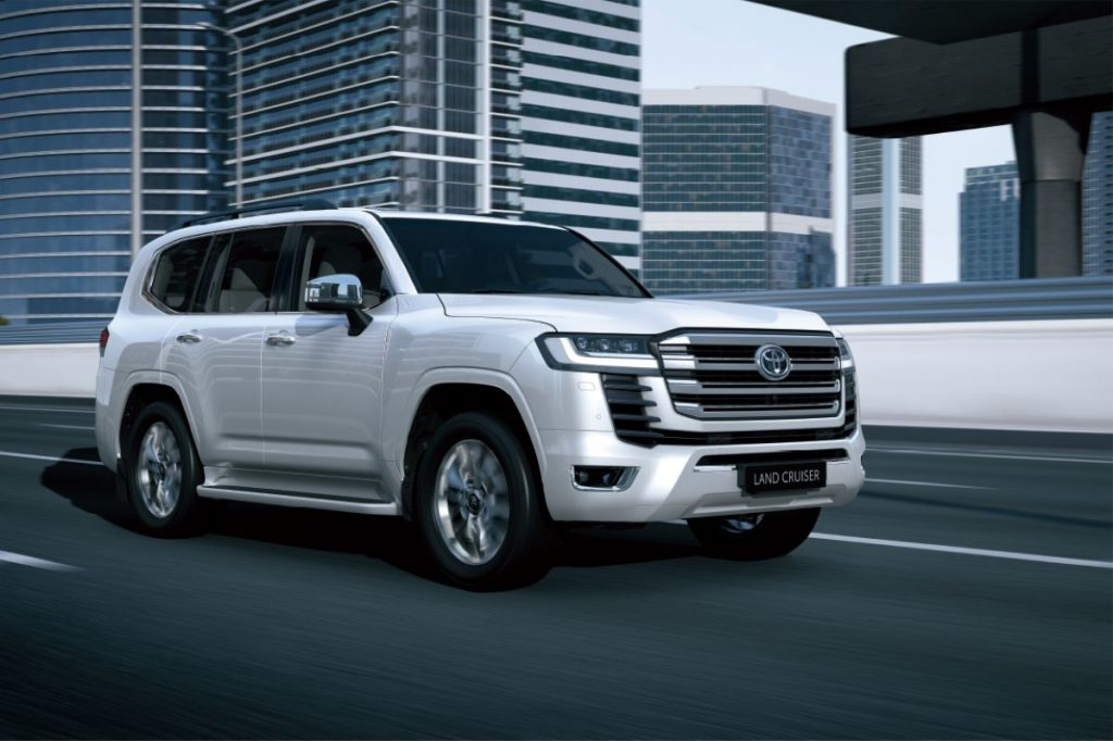 White 2022 Toyota Land Cruiser driving by tall buildings