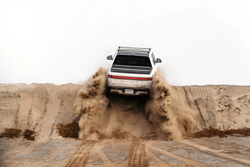 White Rivian R1T driving up a sand dune