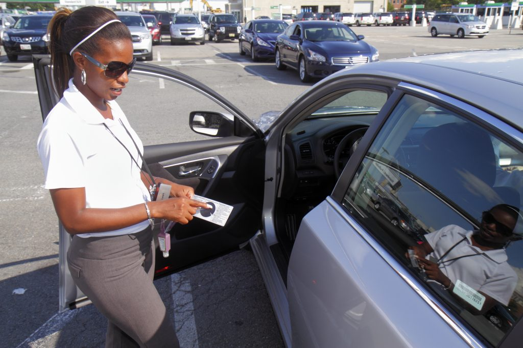 Woman Inspecting Car for Damages or Dents