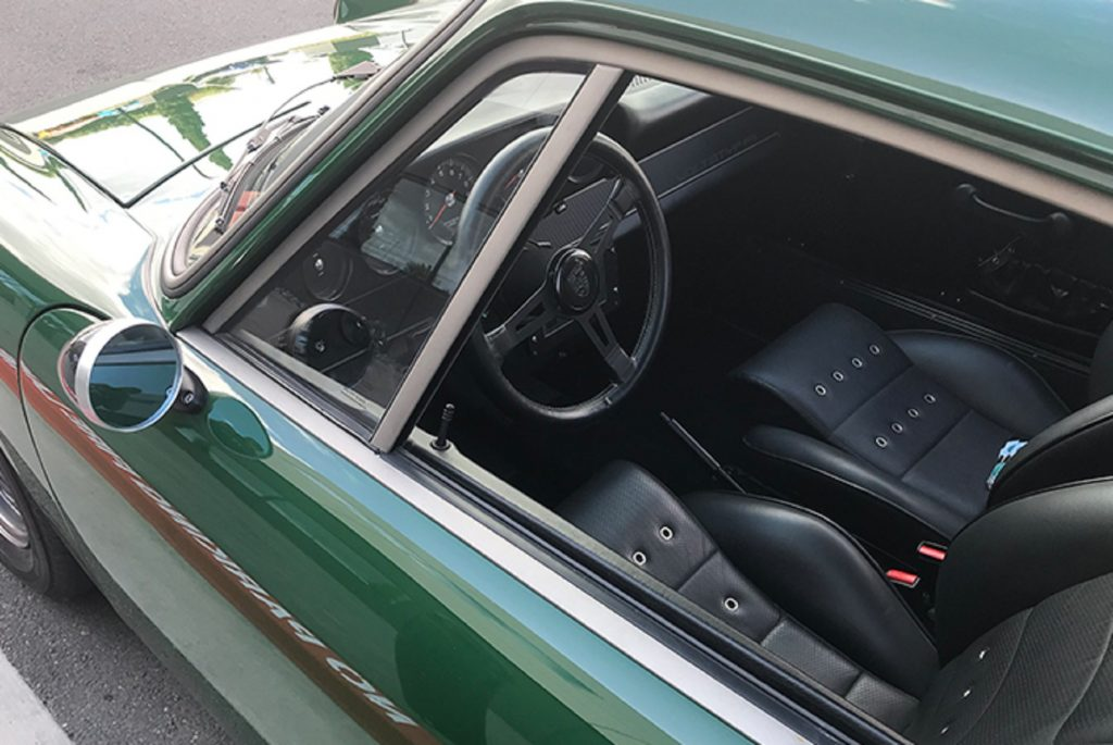 The black-leather-upholstered front seats and black dashboard of Zelectric's green 'Tesla Porsche' 1968 Porsche 912 seen through the driver's side window