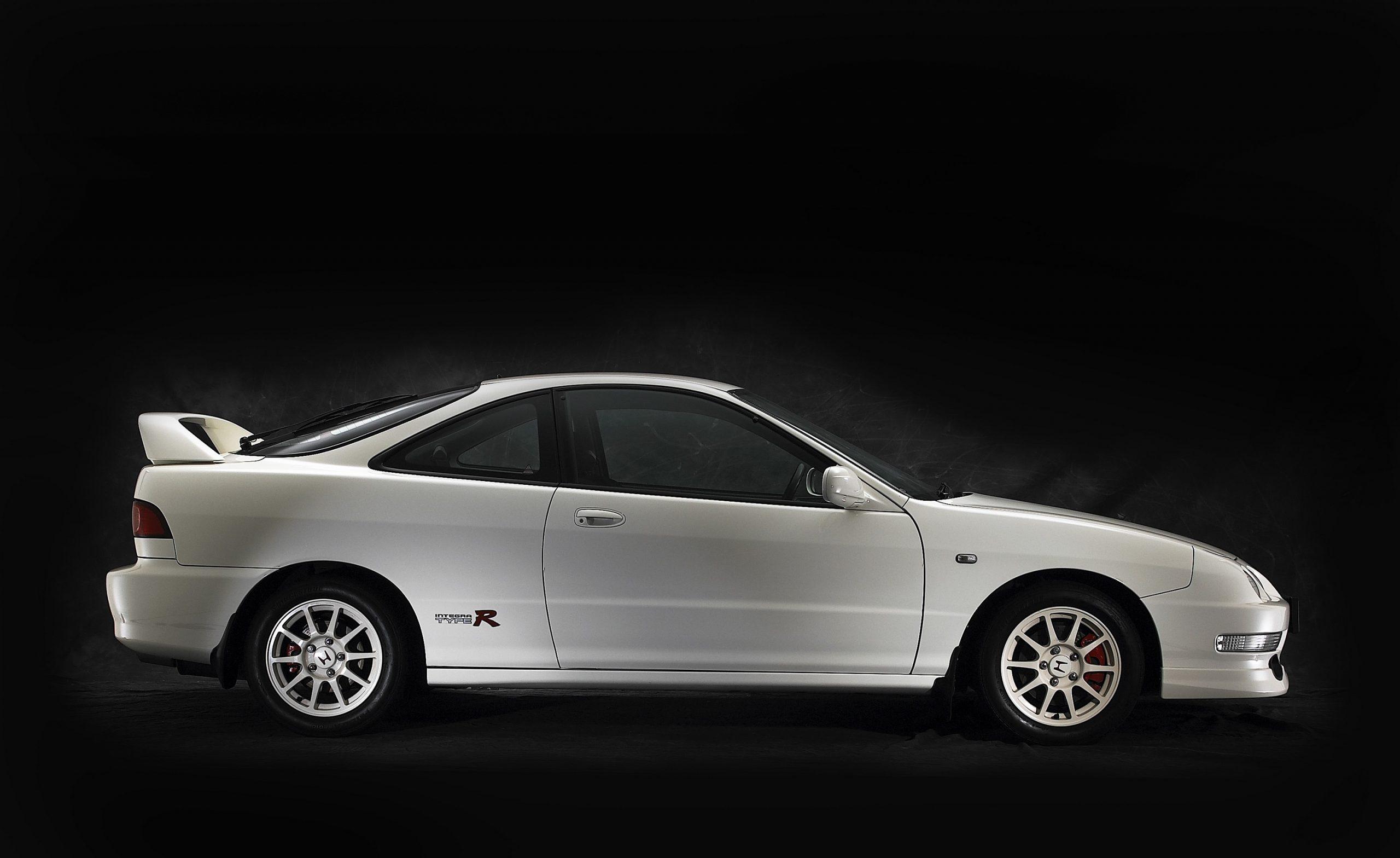 A white Acura Integra Type R shot in profile against a black studio background