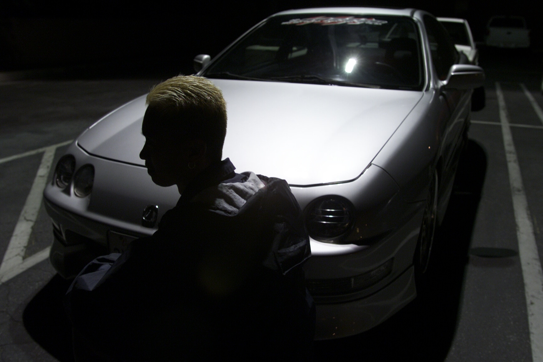 A '90s white Acura Integra and its driver shot from the front 3/4