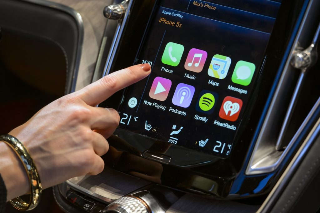 A visitor presses the new Apple's CarPlay touch-screen commands inside the Volvo Estate concept car displayed at the Swedish carmaker during the press day of the Geneva Motor Show in Geneva, on March 4, 2014.