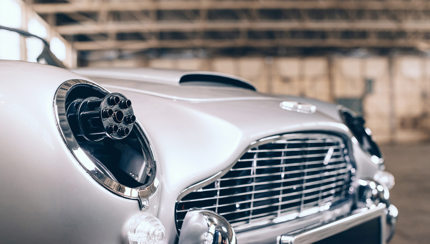 The drop-down headlights of The Little Car Company's Aston Martin toy car features fake spinning machine guns