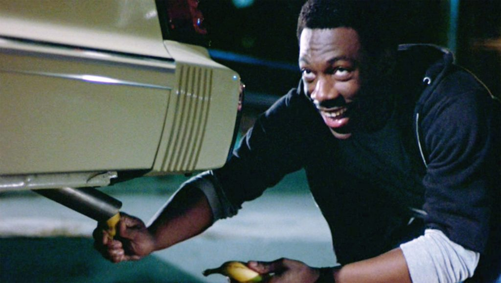 """The movie """"Beverly Hills Cop"""", directed by Martin Brest. Seen here, Eddie Murphy as Det. Axel Foley sticking a banana into the tailpipe of a 1983 Mercury Marquis sedan"""