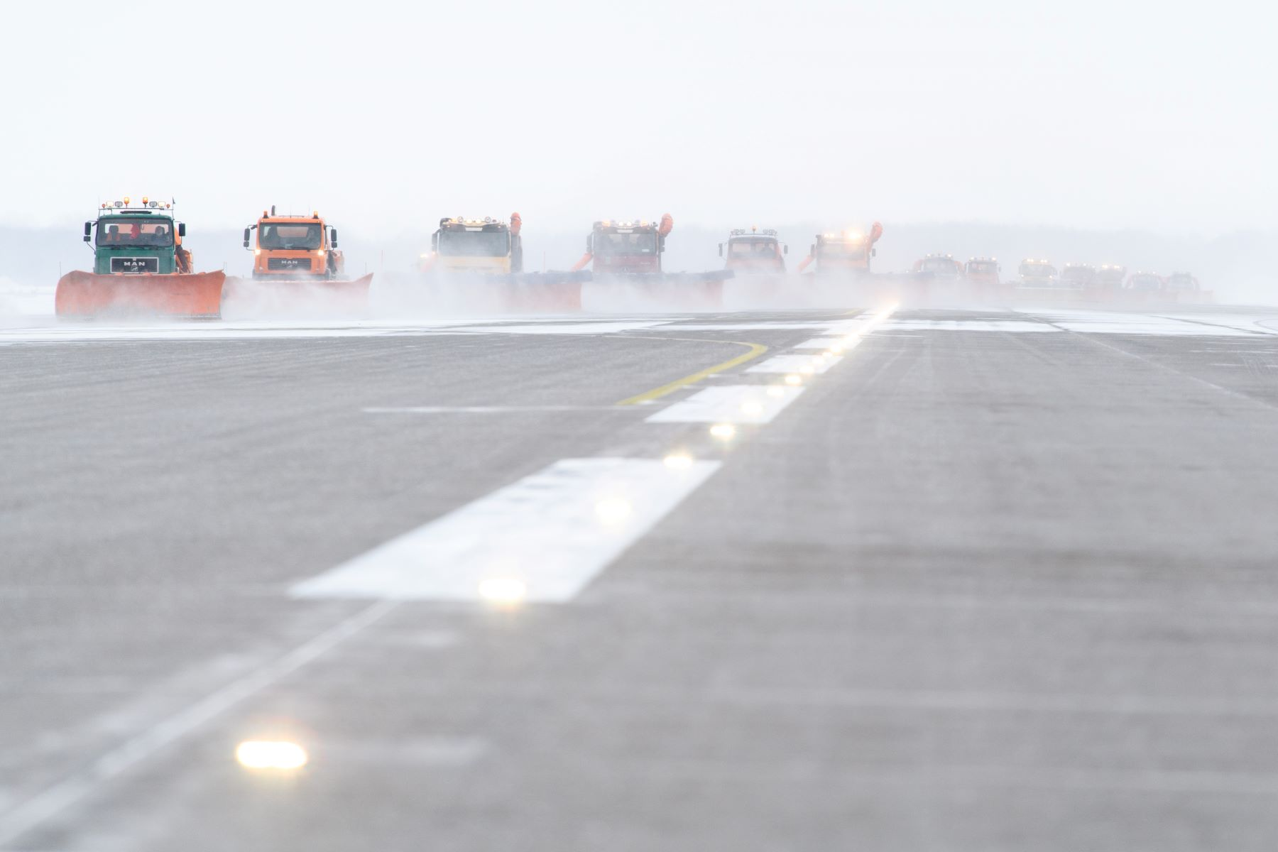 The Munich Airport covered in black ice as snow ploughs clear the runway