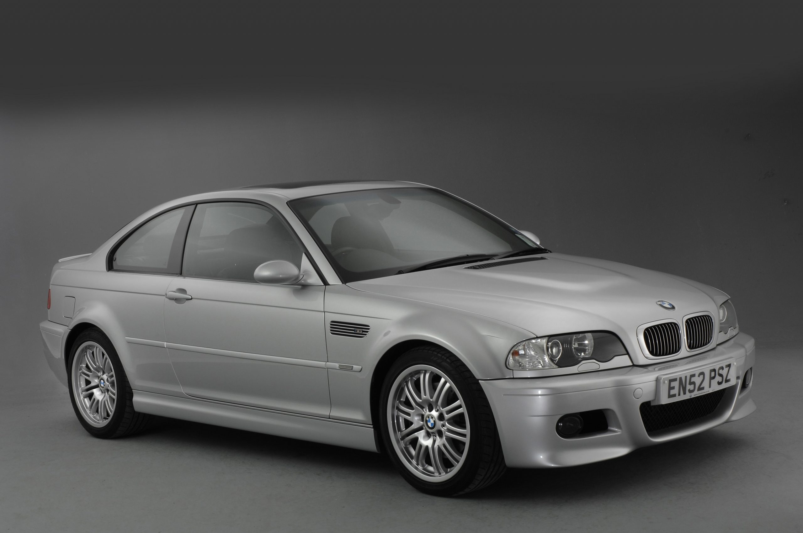A silver E46 BMW M3 shot from the front 3/4 in the studio