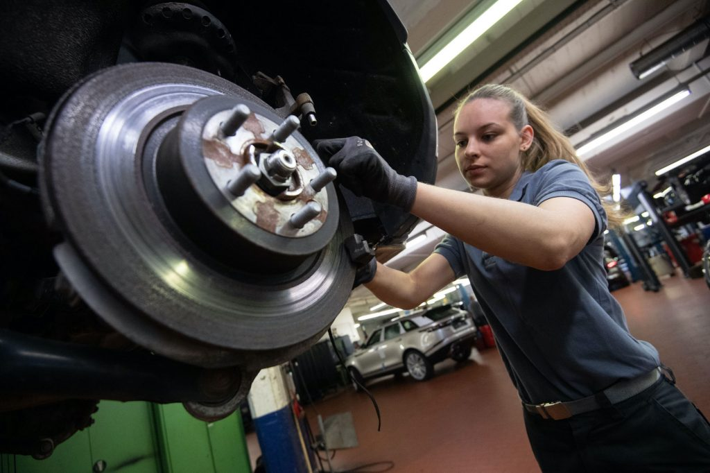 An auto mechanic changes the brake disc of a Range Rover Evoque in a garage.