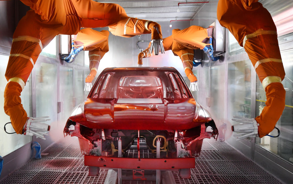 Robotic arms spray paint a car body shell. When buyers order a car from the factory they get to choose the paint color .