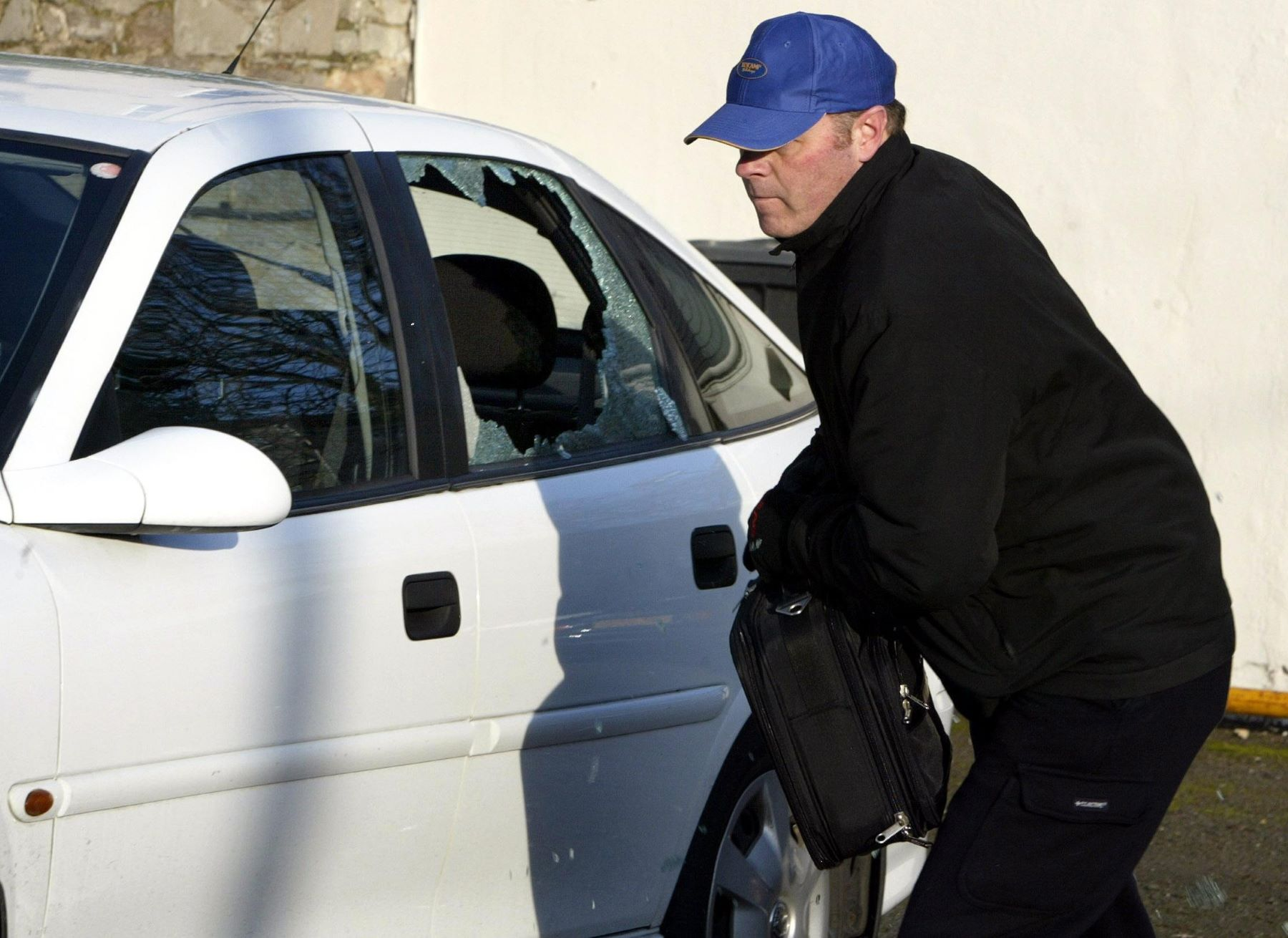 A car thief in a blue baseball cap breaking into a vehicle for a police demonstration