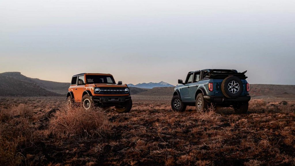 An orange and a blue Ford Bronco sit on a plain with mountains in the background.