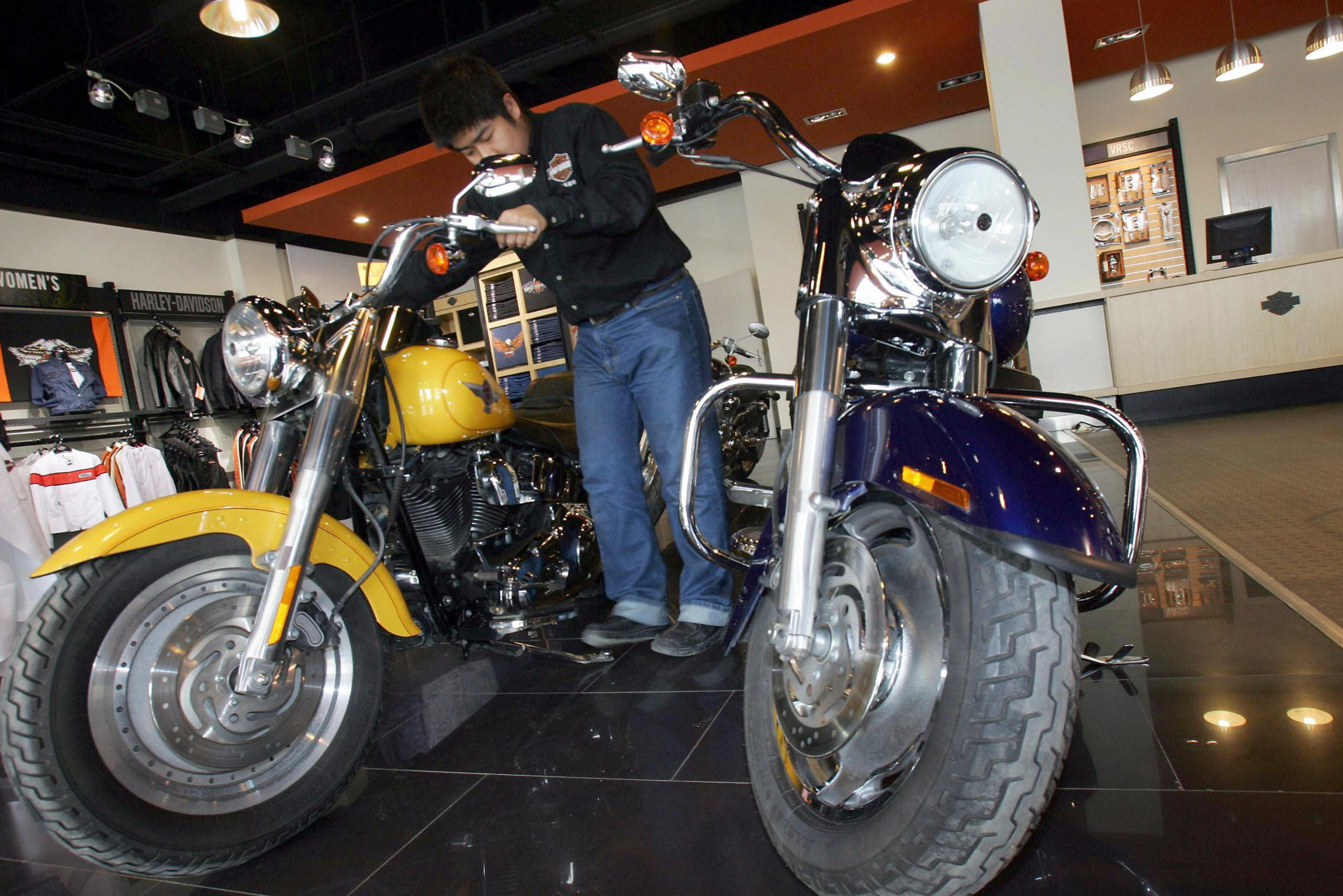 A salesman arranges one of the Harley-Davidson's bikes on display