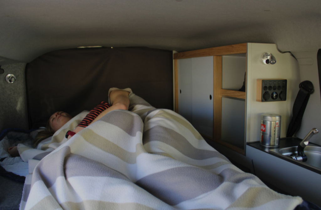 a couples sleeps cozy in the bed of the small camper van