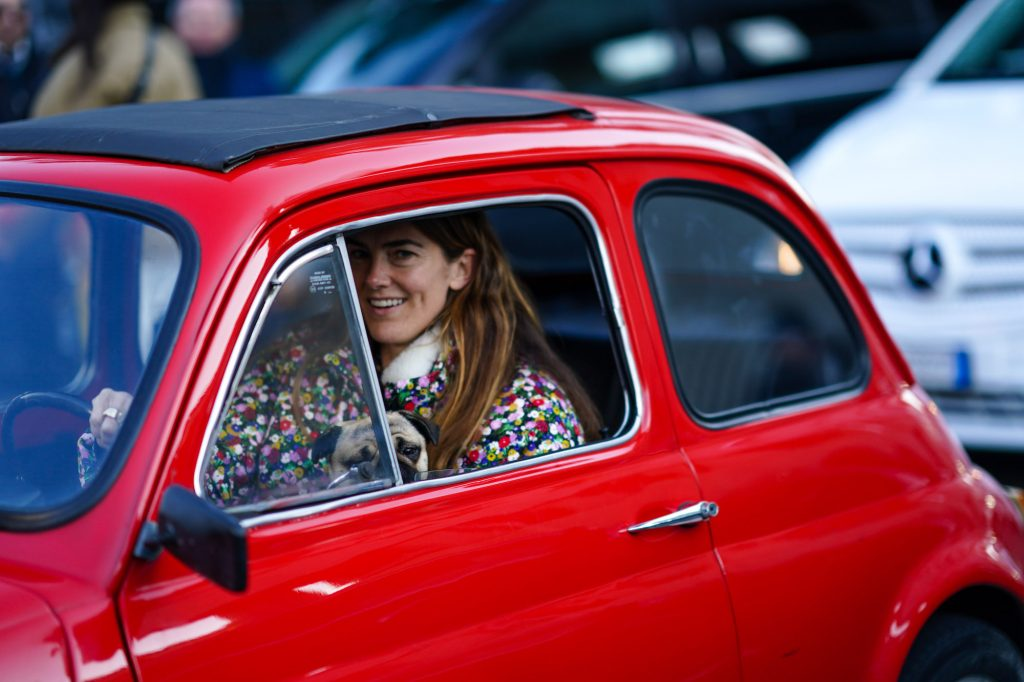 A smiling woman driving a red car in Italy in January 2020