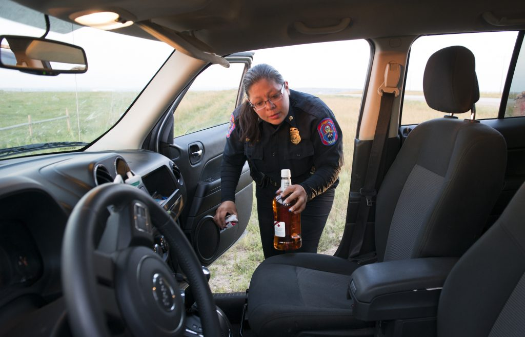 A man is arrested for drunk driving while police Sgt. Dawn White removes an open bottle of whiskey from his car in North Dakota