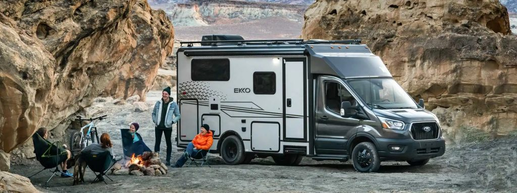 The Winnebago Ekko rules the small RV world. This photo shows people gathered a fire pit with the ekko in the background.