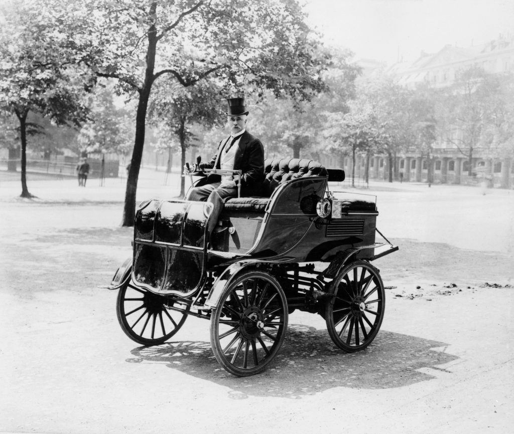a man in an electric car circa 1899. This car is very similar to the Electric Vehicles Company car that was involved in the first car accident death in America in New York City in 1899.