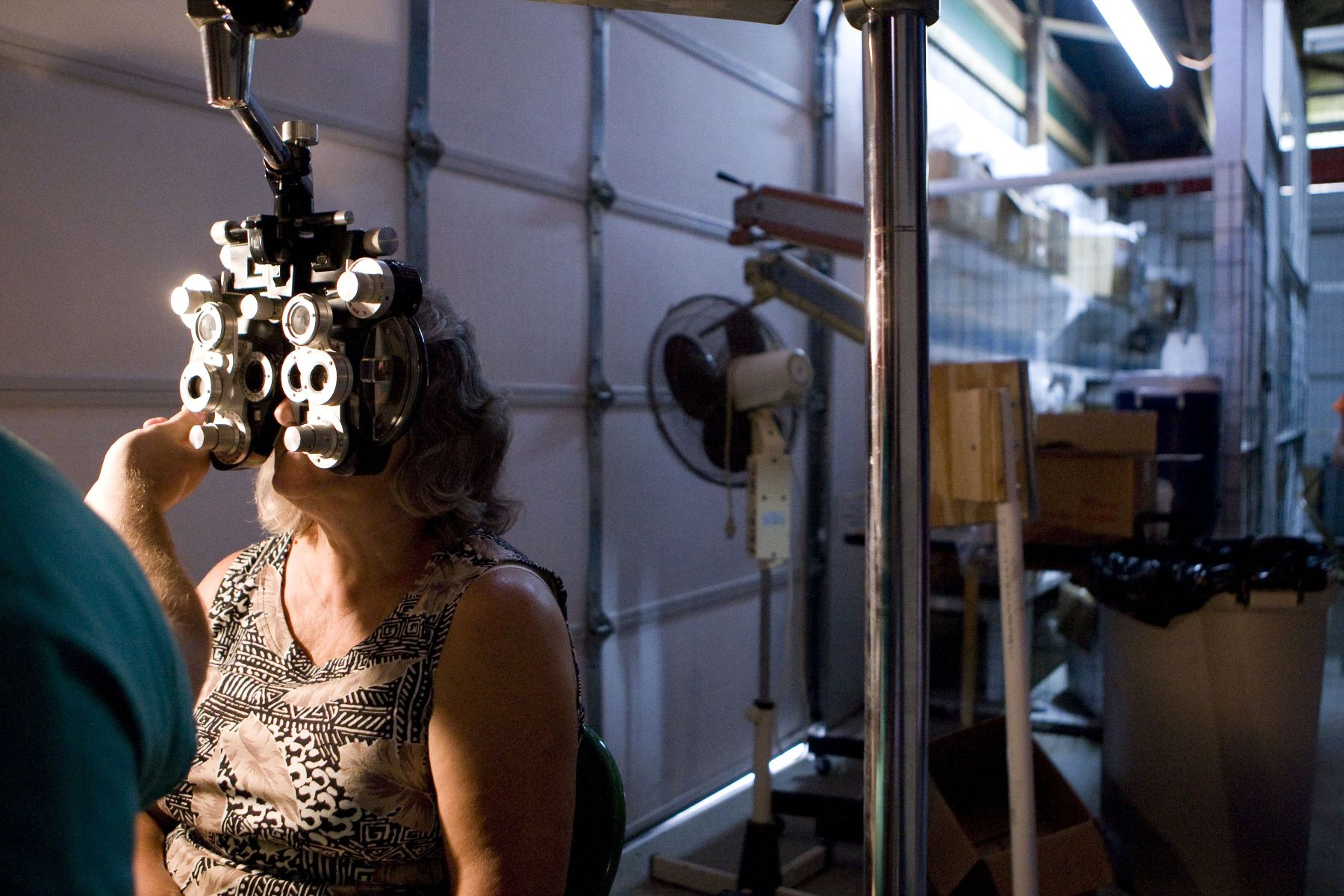 A woman undergoing an eye exam and having her eyes dilated