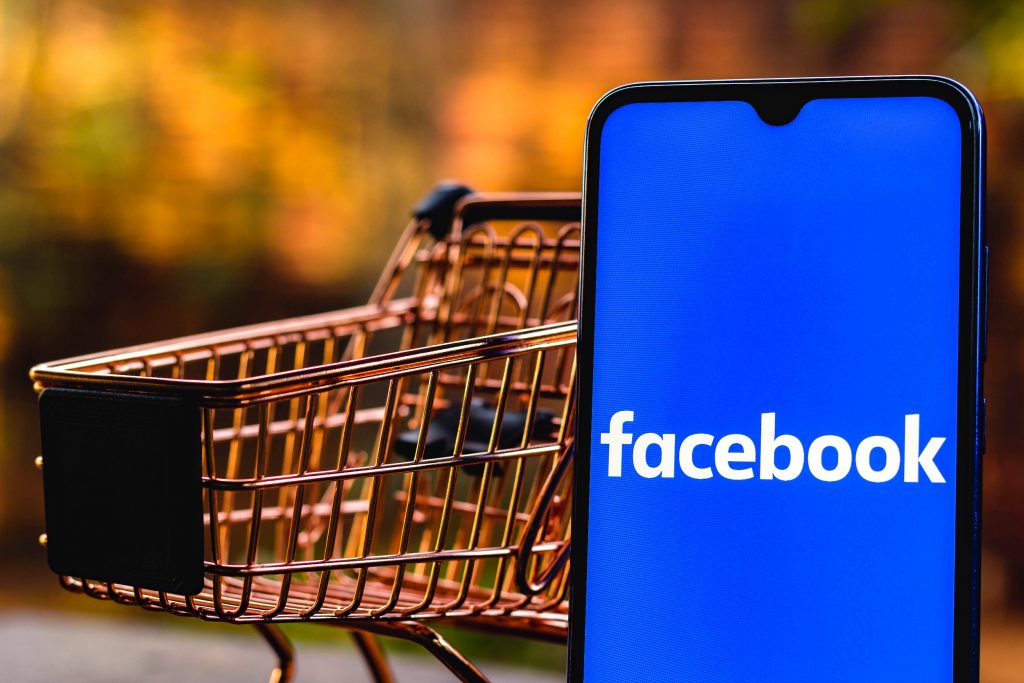 a Facebook logo seen displayed on a smartphone along with a shopping car