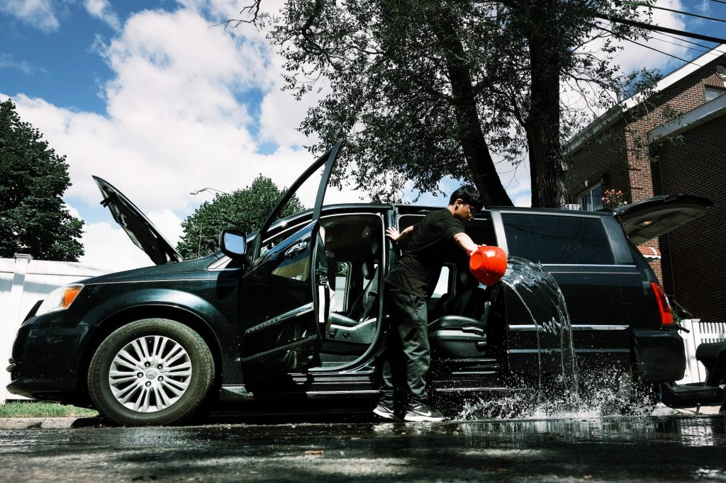 A teen cleans a flooded-damaged car in New York City after Hurricane Ida