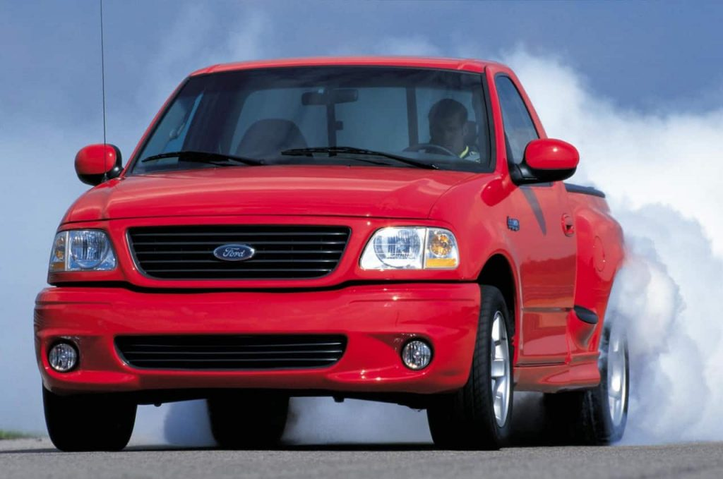 A red Ford Lightning does a burnout