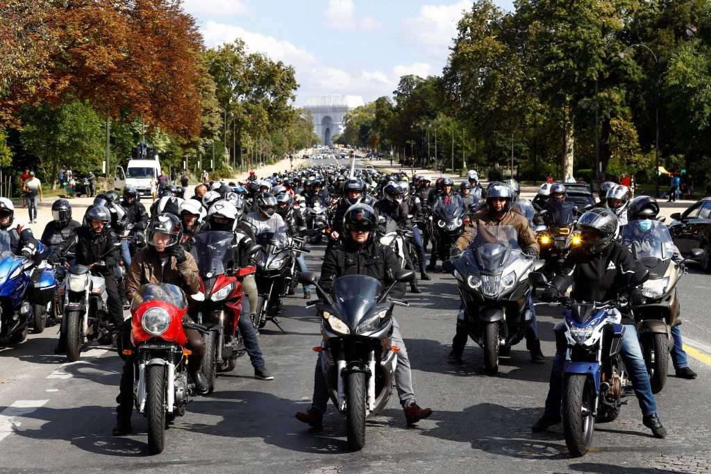 Motorcyclists gather, as the Arc de Triomphe, wrapped in silver-blue fabric as it was designed by late artist Christo, is seen in the background, during a demonstration against a parking reform for Paris which will impose paying parking for non-electric motorcycles and scooters, on September 18, 2021, in Paris.