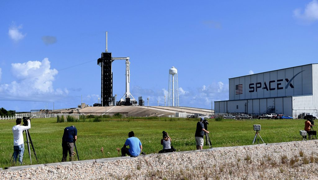 Media photographers set up cameras to take the launch of the Falcon 9 rocket and a Crew Dragon capsule