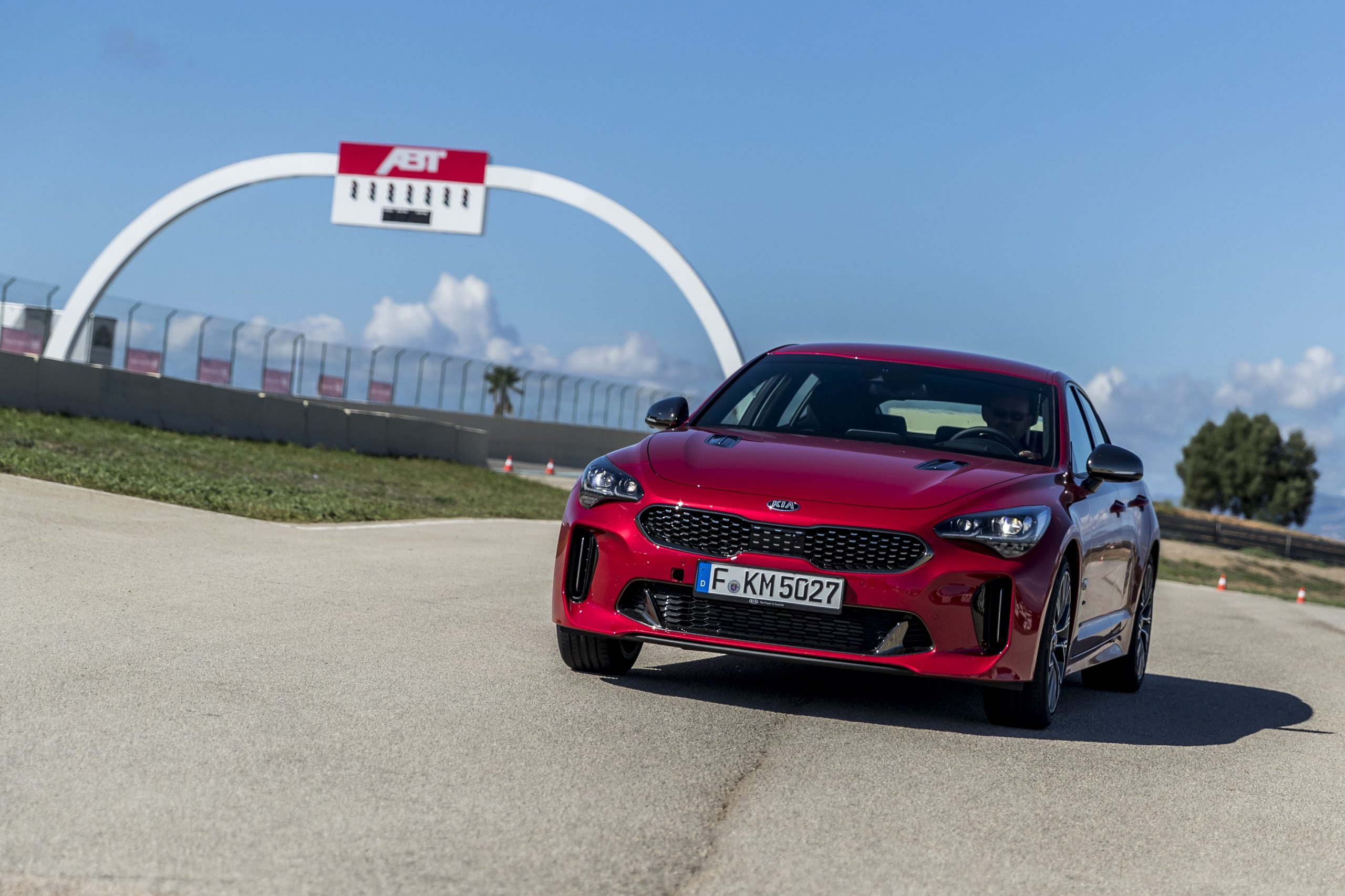 A red Kia Stinger GT on a race track shot from the front 3/4 angle