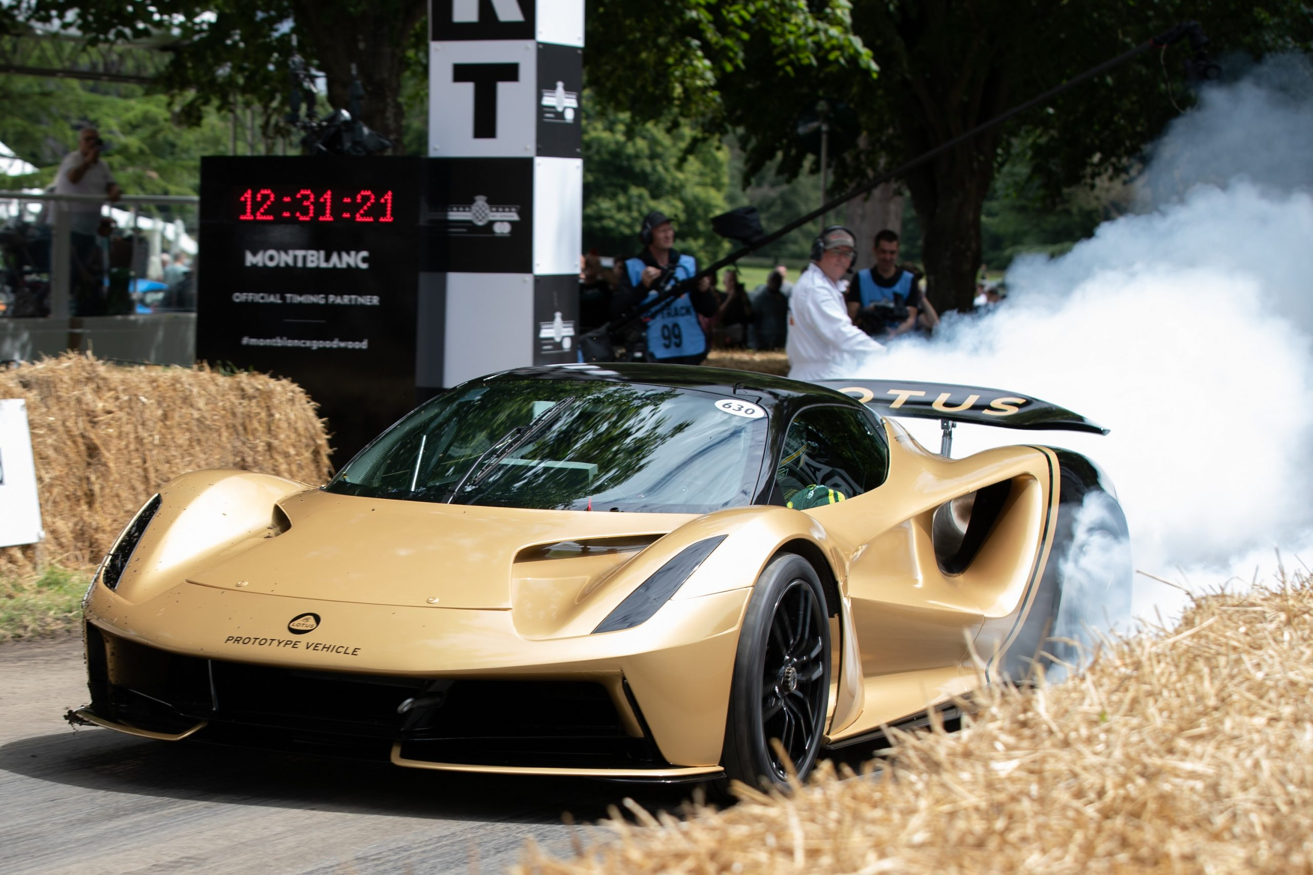 A gold Lotus Evija does a burnout at the start of its lap at the Goodwood Festival of Speed, shot from the front 3/4