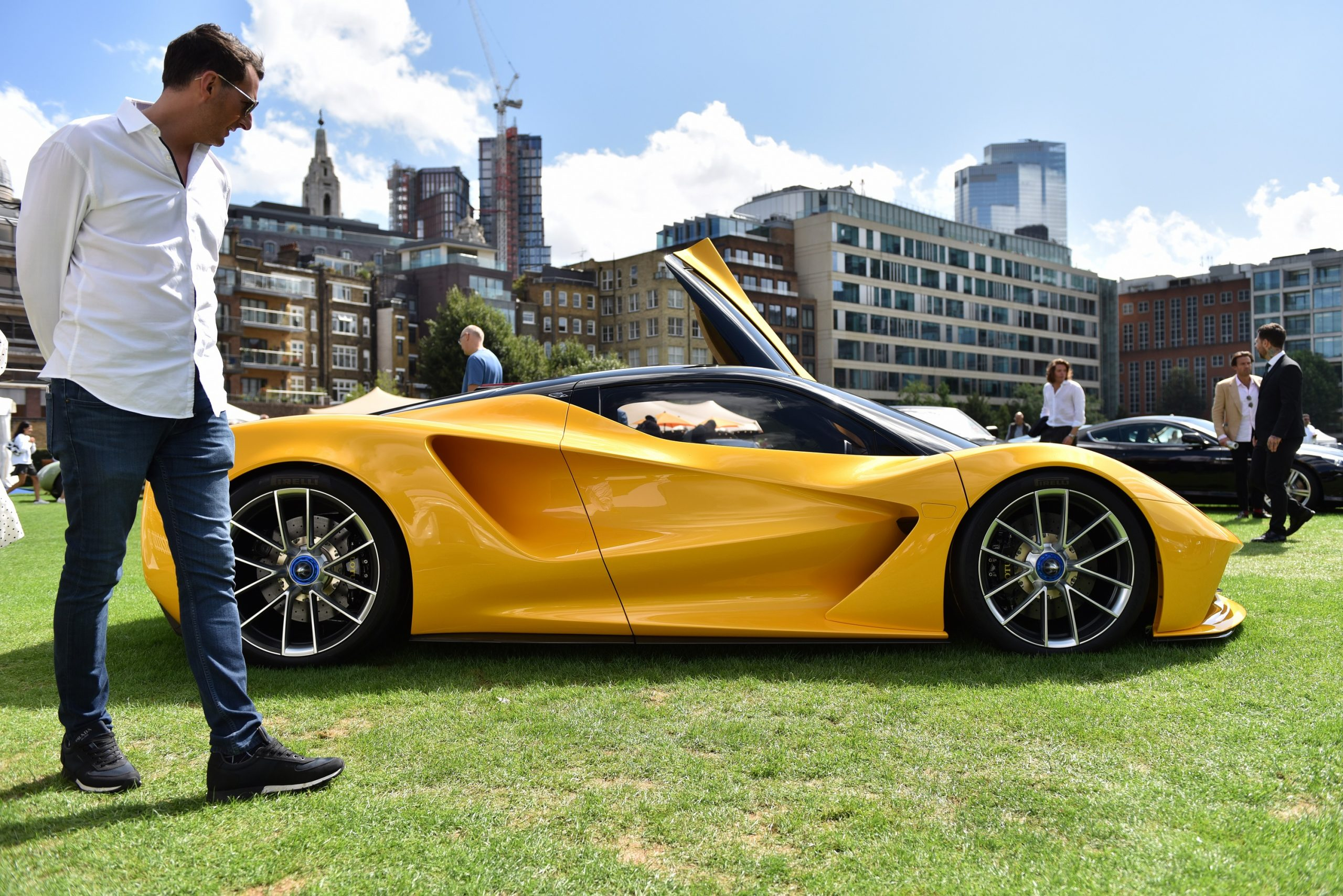 A yellow Lotus Evija is admired by a passerby at a concourse event, shot in profile