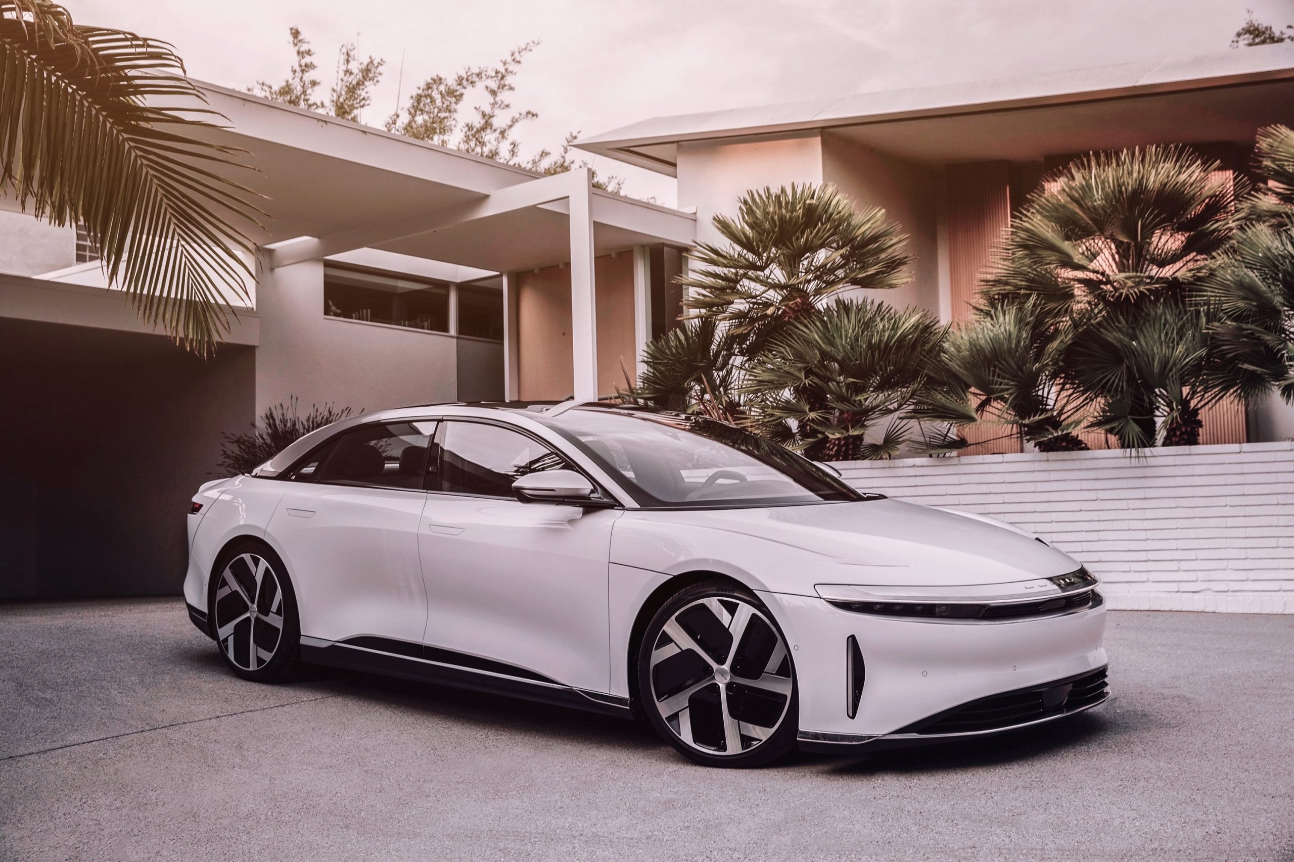 A white Lucid Air luxury EV shot from the front 3/4 angle in a driveway with palms in the background