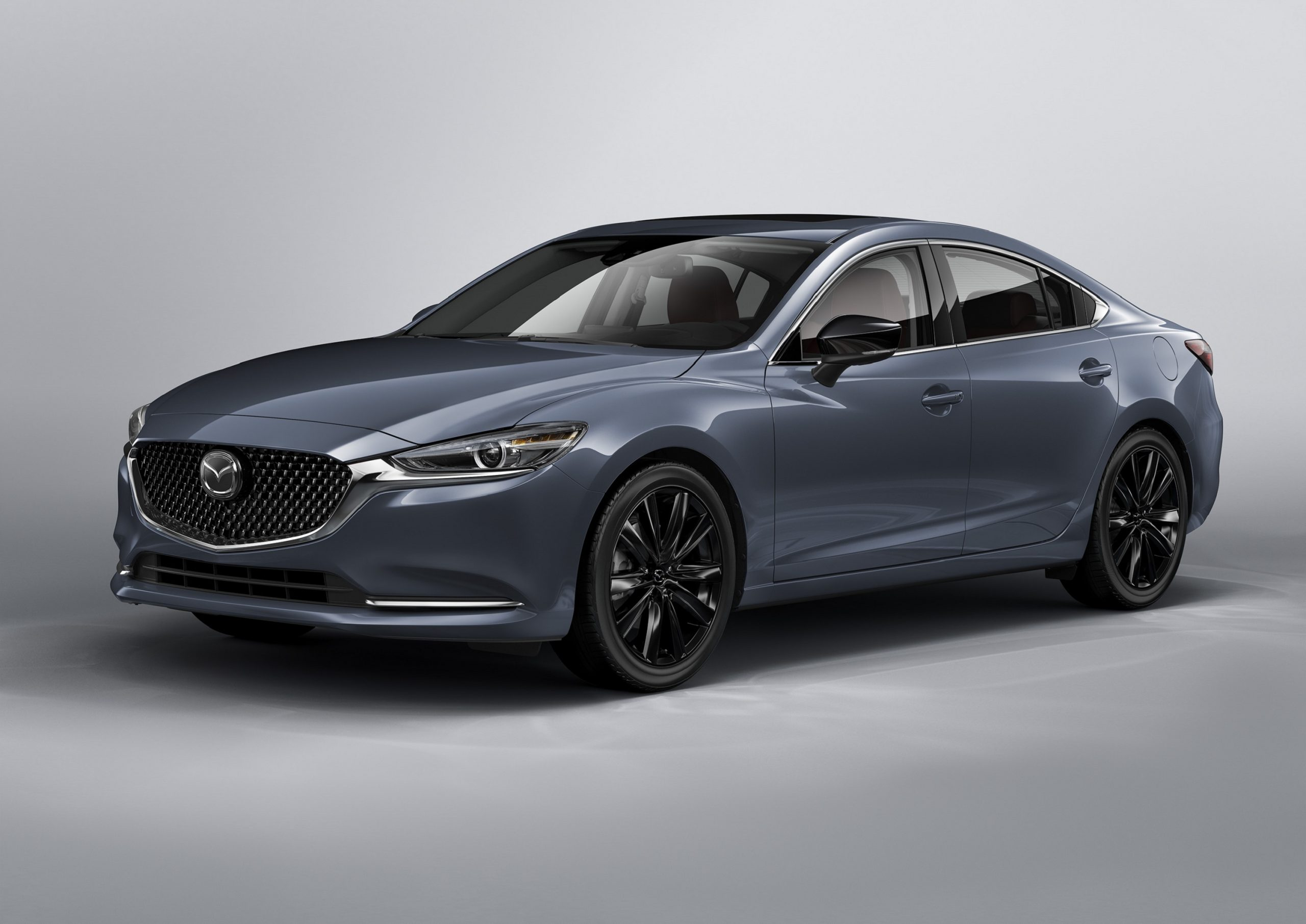 A grey 2021 Mazda 6 sedan shot from the front 3/4 angle in a studio