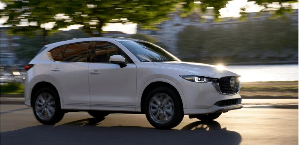 A white 2022 Mazda CX-5 driving by water.