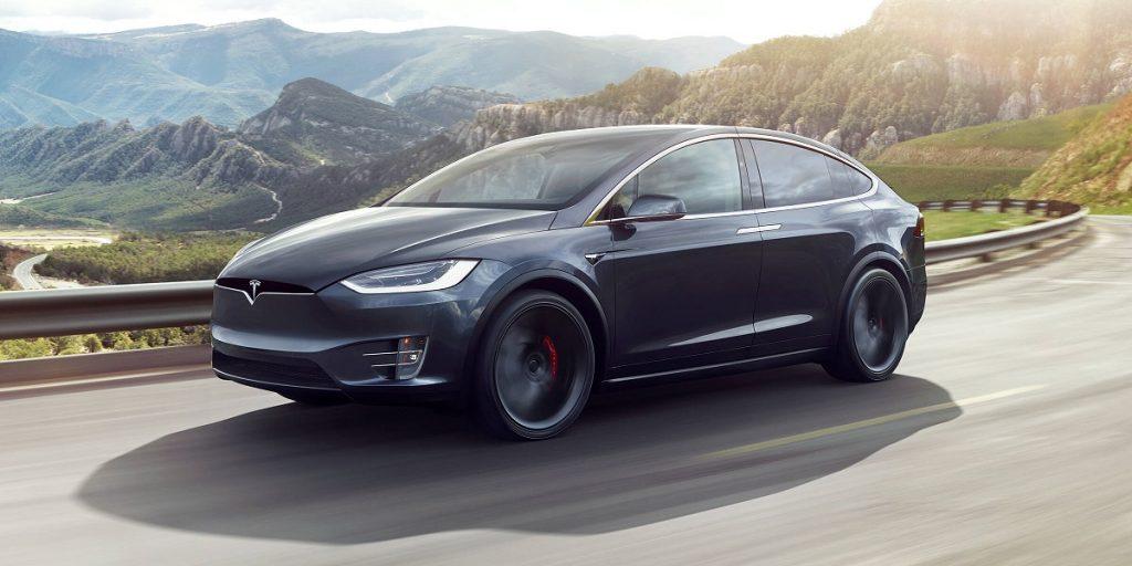 A dark gray Tesla Model X driving past mountains.