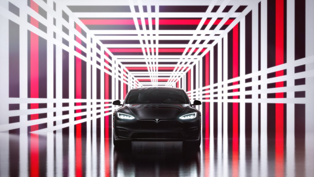 A black Tesla Model S Plaid in a plaid-patterned photo booth