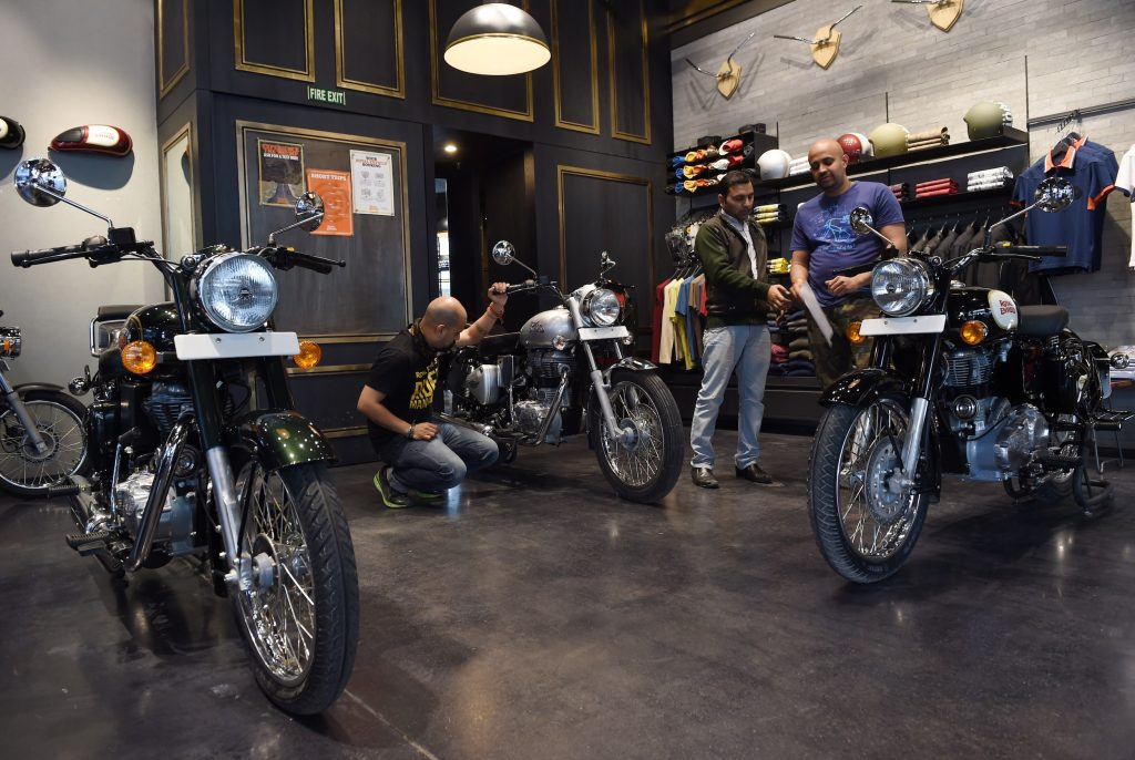 In this photograph taken on February 13, 2015, Indian customers and salesmen look at Royal Enfield motorcycles at a showroom in New Delhi.