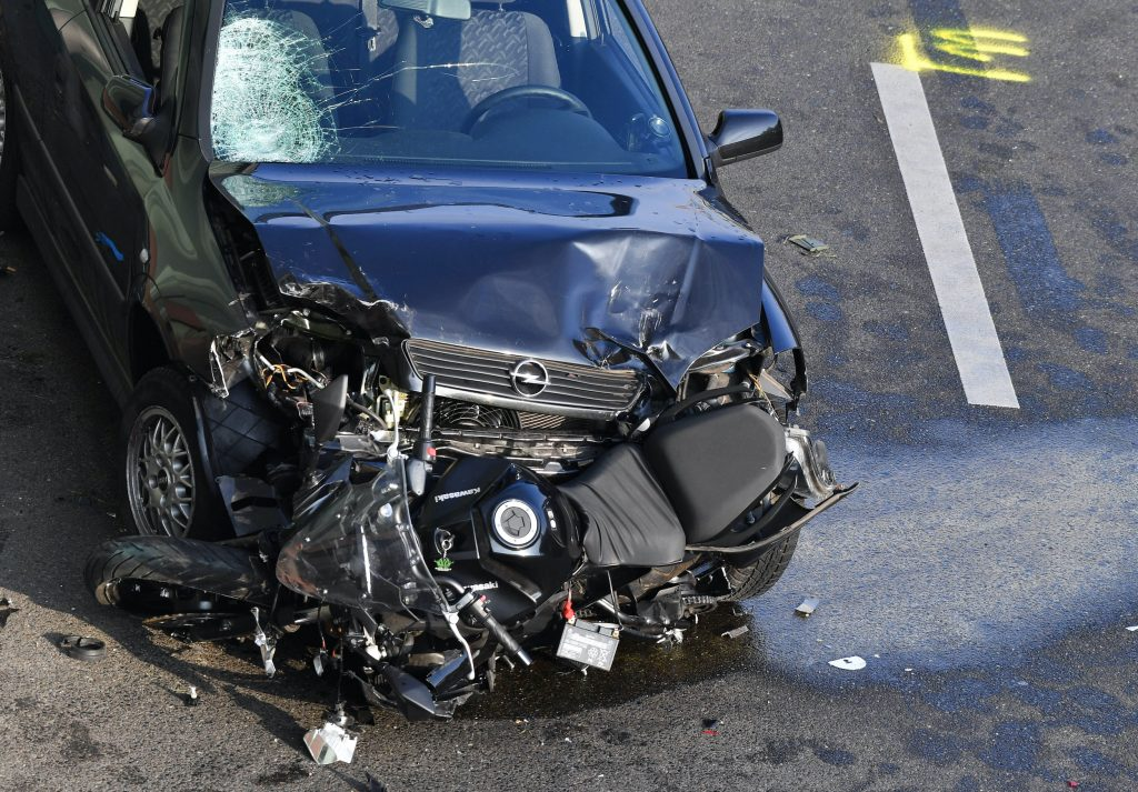 A broken car and a destroyed motorcycle are standing on the Berlin city motorway A100 near the exit Alboinstraße.