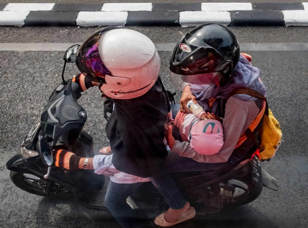 A motorcycle passenger feeds a baby a bottle of milk in Jakarta on August 9, 2017