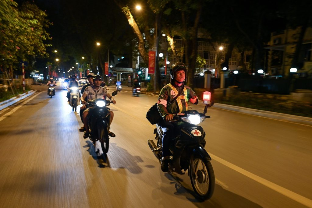 This photograph was taken on May 12, 2020, shows Grab motorcycle rider Pham Quoc Viet (R) riding his motorcycle during a night patrol to help traffic accident victims on the streets of Hanoi.