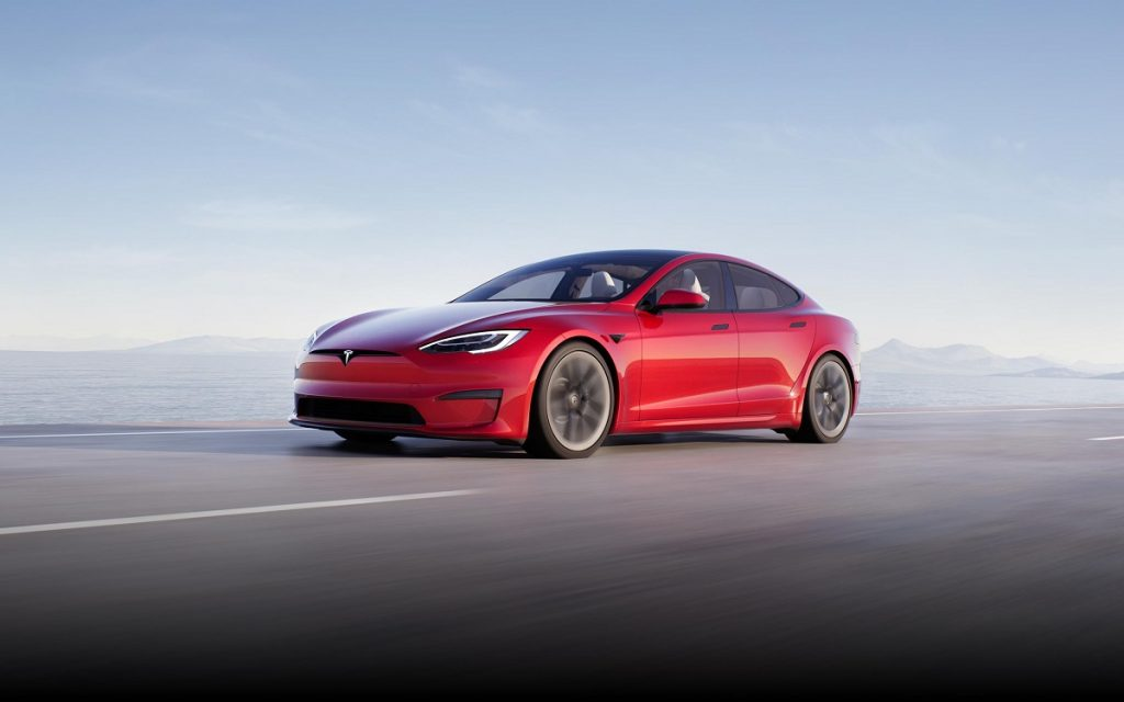 A red 2021 Tesla Model S driving down a road.