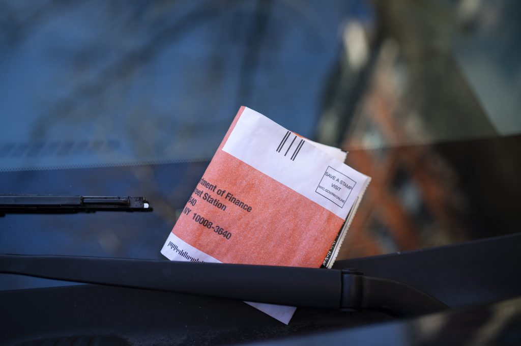 A parking ticket on the windshield of a vehicle in New York City