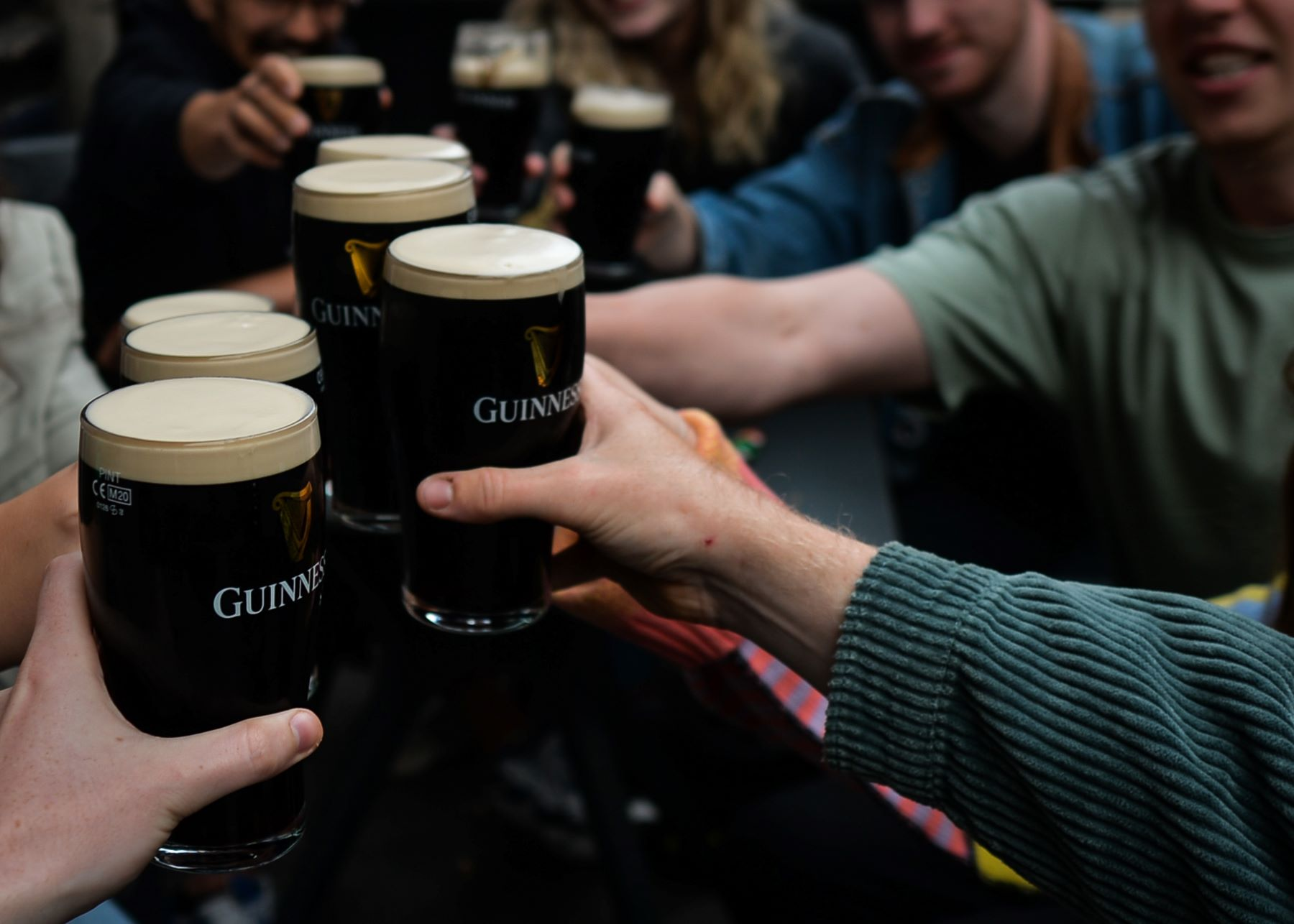 A group of friends drinking Guinness beer in a pub in Dublin, Ireland