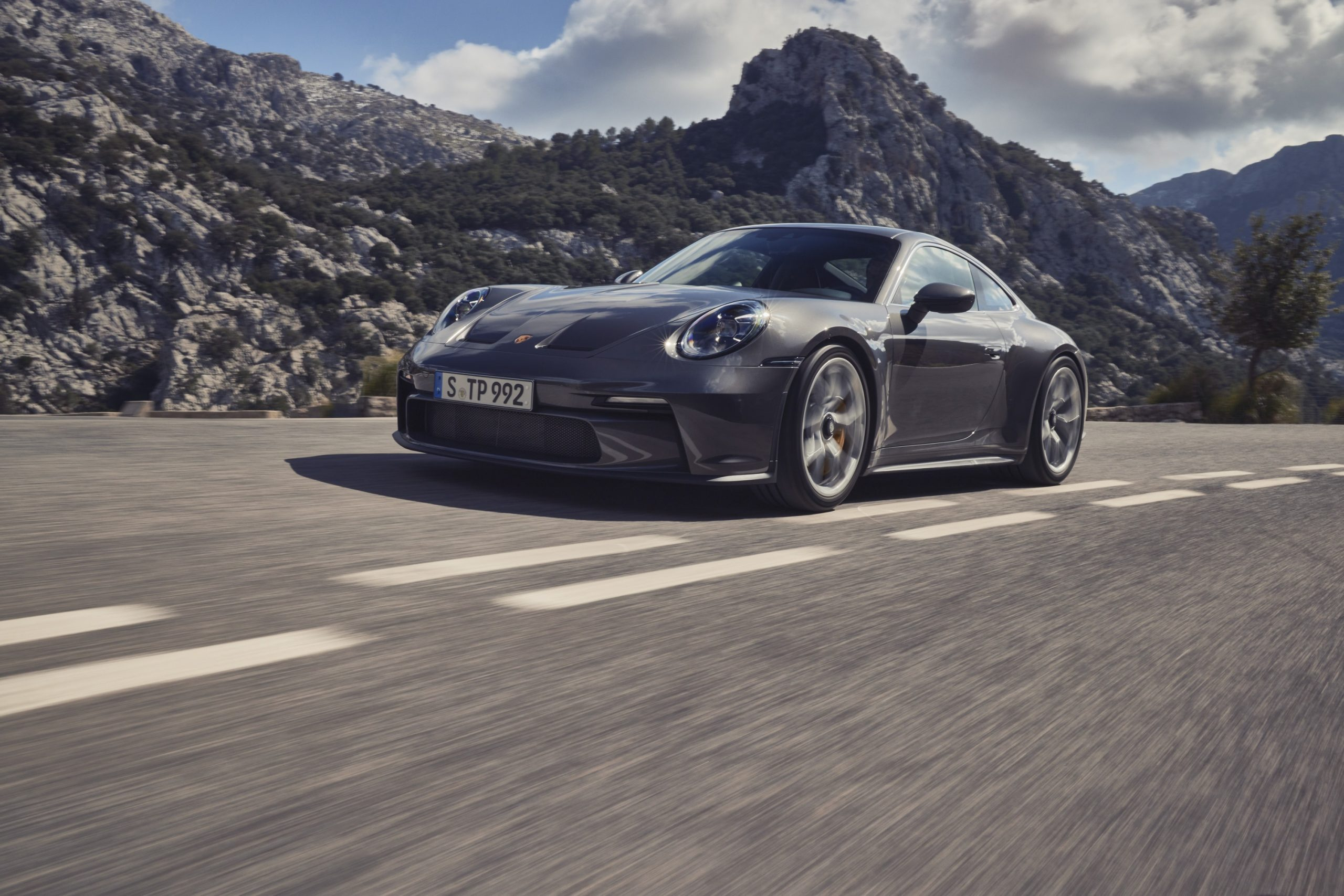 A grey 2022 Porsche 911 GT3 in Touring specification with no wing, shot from the front 3/4 angle on a canyon road