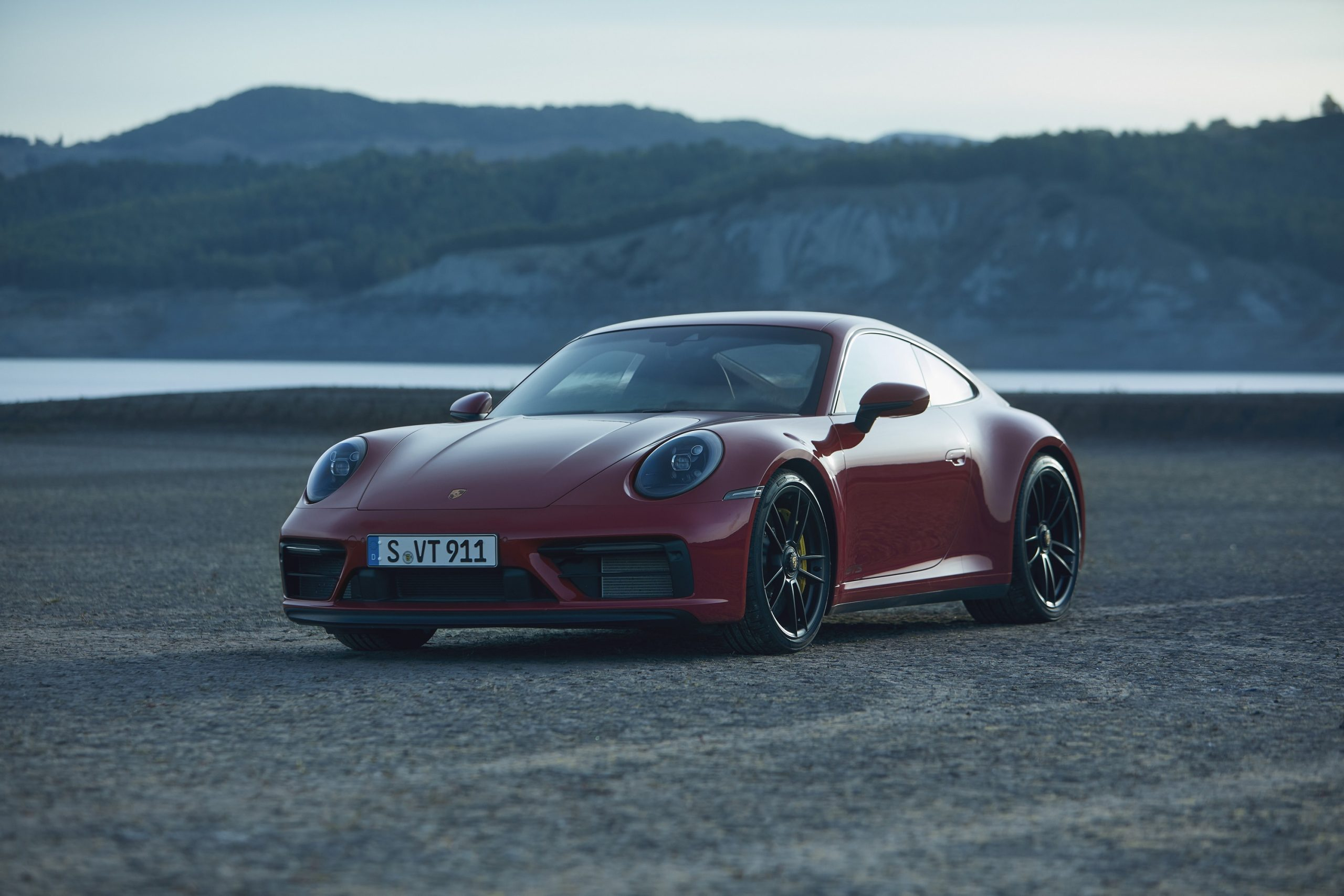 A red Porsche 911 GTS on a beach at sunset, shot from the front 3/4