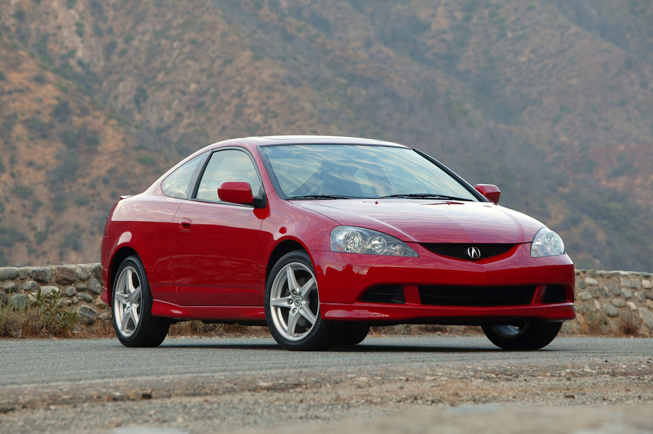 A red Acura RSX Type S shot from the front 3/4 on a canyon road